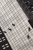 Some workers who wash the windows of an office building Stock Photos