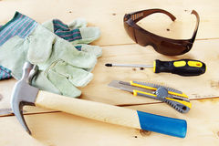 Some working tools with protective gloves and glasses. Lie on wooden background Stock Images