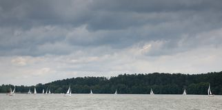 Some yachts sailing under stormy sky. Against dark forest background stock photography
