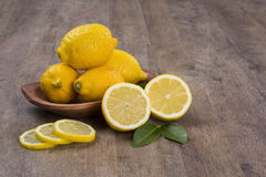 Some yellow lemons over a wooden surface. Royalty Free Stock Image