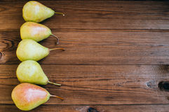 Some yellow pears are on the wooden table. There are some yellow pears are on the wooden table stock photos