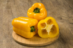 Some yellow peppers over a wooden surface. Fresh vegetable Royalty Free Stock Photos
