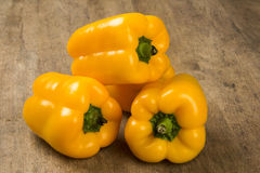 Some yellow peppers over a wooden surface. Fresh vegetable Stock Photos