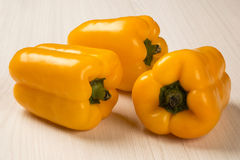 Some yellow peppers over a wooden surface. Fresh vegetable Royalty Free Stock Photo