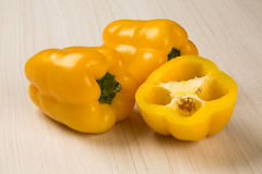 Some yellow peppers over a wooden surface. Fresh vegetable Royalty Free Stock Photography