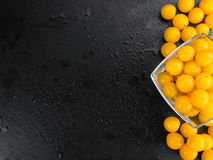 Some Yellow Tomatoes on a dark slate slab. Some fresh Yellow Tomatoes on a vintage slate slab, selective focus, close-up shot stock photography