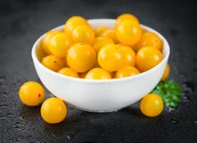 Some Yellow Tomatoes on a dark slate slab. Some fresh Yellow Tomatoes on a vintage slate slab, selective focus, close-up shot royalty free stock photo