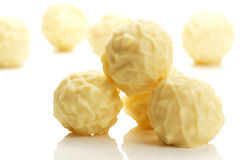 Some yellow truffle pralines in front of others. On white background Stock Photos