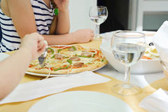 Somebody cutting pizza using pizza knife Stock Photography