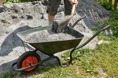 Somebody filling the wheelbarrow. With a grey sand Stock Photo