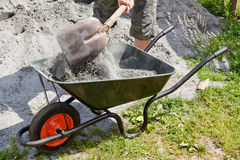 Somebody filling the wheelbarrow. With a grey sand Royalty Free Stock Image
