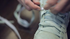 Somebody hands without manicure laces grey sneakers. stock video