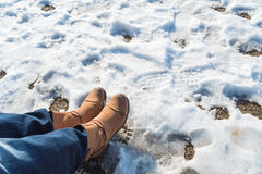 Somebody legs with warm winter shoes on snow. Footwear for cold days Royalty Free Stock Image