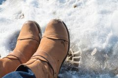 Somebody legs with warm winter shoes on snow. Footwear for cold days Royalty Free Stock Images