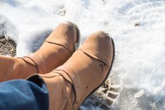 Somebody legs with warm winter shoes on snow. Footwear for cold days Royalty Free Stock Photography