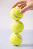 Somebody making tennis ball tower. Ball tower. Female hand making a tower out of three tennis balls Royalty Free Stock Images
