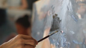 Somebody is painting some picture with paintbrush. Woman on canvas. close up macro stock video footage