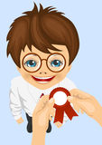 Somebody pins award ribbon to chest of schoolboy won school competitions. Standing on blue background Royalty Free Stock Images