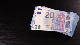 Somebody puts pack of 20-euros banknotes on the black table stock video footage