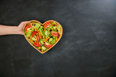 Somebody showing nutrition vegetable healthy food. Somebody hand showing nutrition vegetable healthy food in wooden heart shaped plate on black chalkboard with Royalty Free Stock Photography
