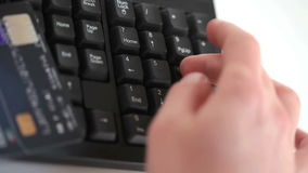 Somebody typing on a keyboard with a credit card stock footage