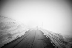 Somebody is walking on road leading through scenic countryside, Snow & fog at Grossglockner mountain, Austria. Enjoy the views from Großglockner Hochalpenstraß Royalty Free Stock Photography