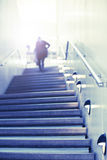 Somebody walks up the stairs to the light. Some person walks up concrete stairs to toward the light at the top. Concept of success stairs stock image