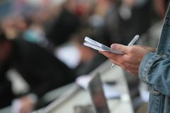 Somebody write in his noticebook. Somebody write something in his noticebook during reporting from a sports event football game Royalty Free Stock Image