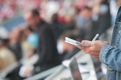 Somebody write in his noticebook. Somebody write something in his noticebook during reporting from a sports event football game Stock Photography