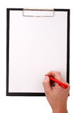 Somebody writing on a clean paper. Black clip board with blank paper and a hand holding red pen Stock Photo