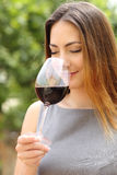 Somelier woman smelling red wine. Somelier woman smelling and tasting red wine with a green background Stock Photography
