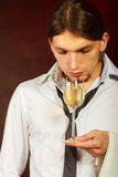 Somellier checking wine quality. Winery alcohol liquor drinking concept. Somellier checking wine quality. Young male waiter holds wine glass Royalty Free Stock Image