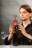 Somellier opening bottle with corkscrew. Alcohol liquor degustation winery relax concept. Somellier opening bottle with corkscrew. Male waiter opens wine Royalty Free Stock Image