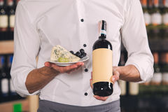 Somellier Wine Business Alcohol Drink Store Concept. Somellier young man holding wine bottle and snacks plate Royalty Free Stock Image