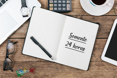 Somente 24 horas, Portuguese text for Only 24 Hours in notebook. Somente 24 horas, Portuguese text for Only 24 Hours, in notebook on office desk with electronic Stock Images