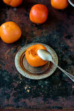 Someon start to eat persimmon on siver plate over rustic surface. Stock Photo