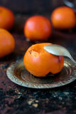 Someon start to eat persimmon on siver plate over rustic surface. Stock Image