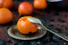 Someon start to eat persimmon on siver plate over rustic surface. Royalty Free Stock Photo
