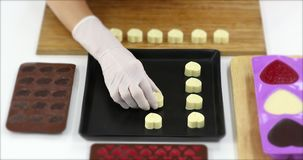 Someone arrange heart shaped chocolates on board. Close up scene video of someone arrange white heart shaped chocolates on wooden board in kitchen, concept for stock video footage