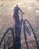 Someone with bicycle shadow on ground.  Stock Photos