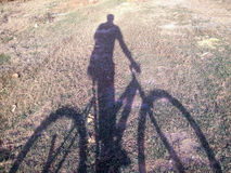 Someone with bicycle shadow on ground.  Royalty Free Stock Image