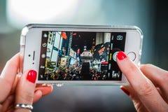 Someone Bierze obrazek z iPhone times square przy nocą Fotografia Royalty Free
