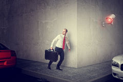 Someone control me. Man escape with handbag and huge cctv royalty free stock photography
