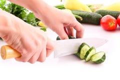 Someone cutting a cucumber Stock Photo