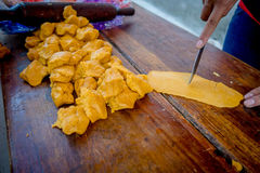 Someone cutting a yellow ready rough on a wooden table. Different forms royalty free stock photos