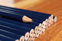 Someone is different. Rows of blunt pencils with only one pencil sharp royalty free stock image