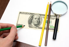 Someone draw dollar by pencils. And magnifier Stock Photos