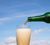 Someone fill glass with beer. On blue sky and clouds background Royalty Free Stock Images