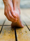 Someone get hurt with tacks, feet walked and push one of this. hand making some massage Royalty Free Stock Photo