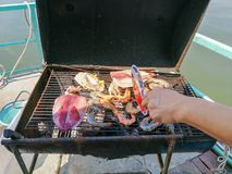 Someone hand winding and grilling seafood, prawn, and squid on t. He steel drum grill barrel. General grilled food Stock Image